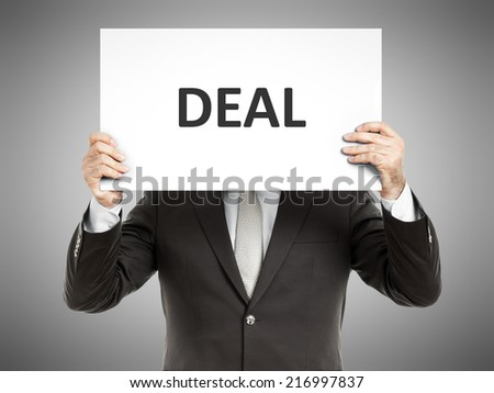 A business man holding a paper in front of his face with the text deal