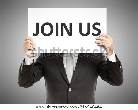 A business man holding a paper in front of his face with the text join us - stock photo