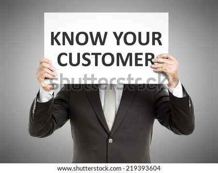 A business man holding a paper in front of his face with the text know your customer - stock photo