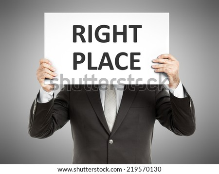 A business man holding a paper in front of his face with the text right place - stock photo