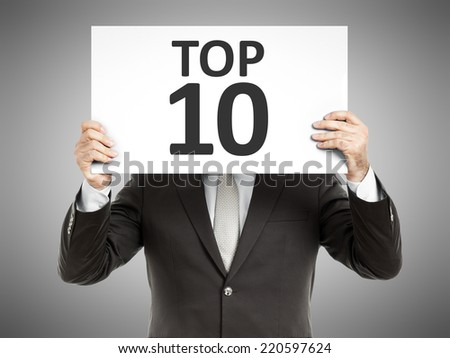 A business man holding a paper in front of his face with the text top 10