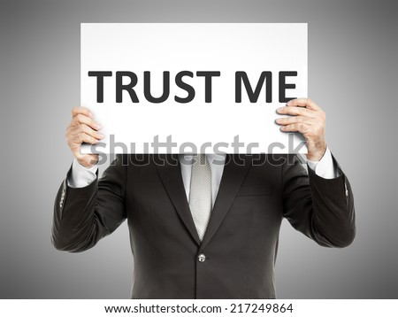 A business man holding a paper in front of his face with the text trust me - stock photo