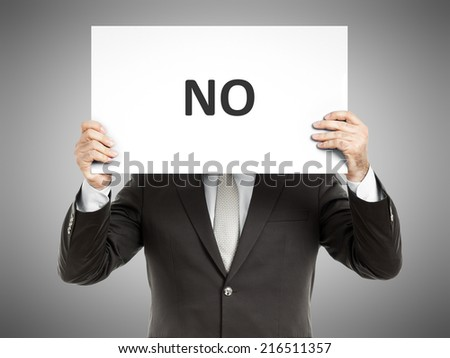 A business man holding a paper in front of his face with the word no