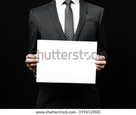 A business man holding a paper. Studio shot