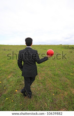 A business man holding a red ball on his hand - stock photo