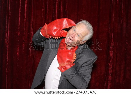A Business Man is attacked by his own Lobster Claw Hands while in a Photo Booth.   - stock photo