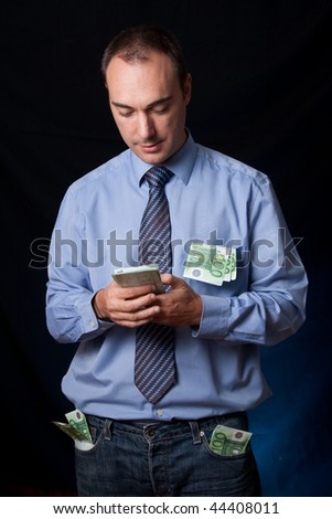 A business man is counting a wad of money. His pocket are full of wads while he's counting another one on his hands. Quiet expression. Conceptual image for business success, rich people, income, ... - stock photo