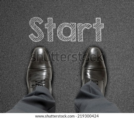A business man is looking down at his feet and there is a text says start - stock photo