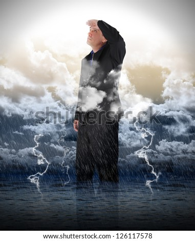 A business man is looking up to bright light in stormy weather for a strength, success or faith metaphor. - stock photo