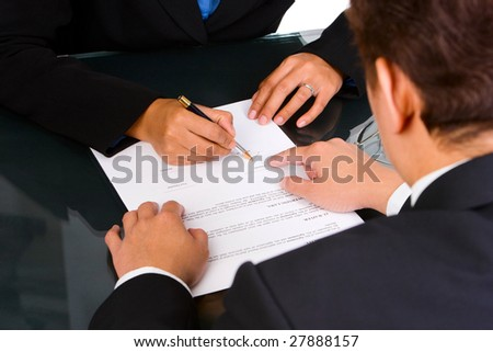 A business man is pointing a place where she should sign the agreement. - stock photo