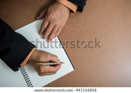 A business man  is writing in a big notepad on a wooden table