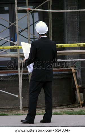 A business man, or contractor or  architecture or building inspector inspects the work and blue prints on new home construction - stock photo