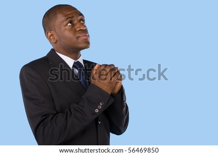 A business man praying and looking up to god - stock photo