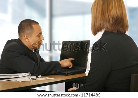 a business man showing blank laptop screen to business woman. focus on the man. concept for business talk, team work, or sales