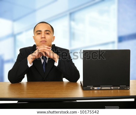 a business man sitting by his office space window next to his laptop waiting for something