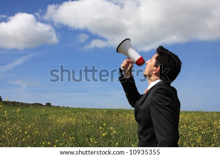 A business man speaking to god with a megaphone - stock photo