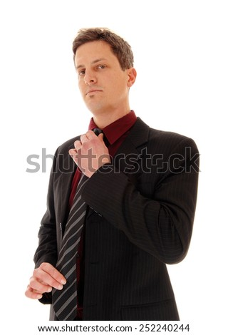 A business man standing in a suit and fixing his tie, looking serious, isolated for white background.