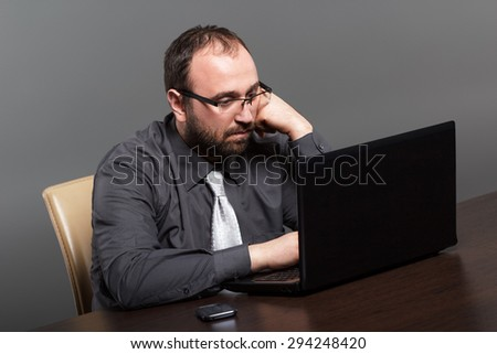 A business man staring at his laptop, deep in thought.
