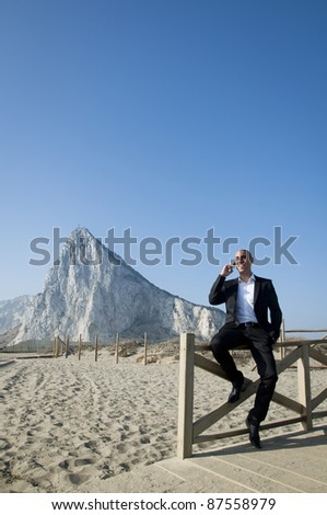 A business man taking a break on the beach talking on the phone