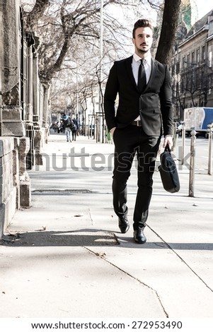 A business man walking down the street in a european city.  - stock photo