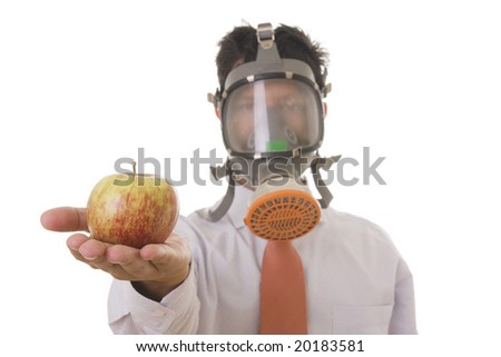 A business man with a mask holding a genetic manipulated apple (focus on the apple) - stock photo