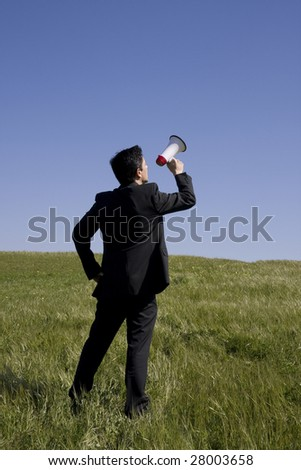 A business man with a megaphone on the meadow - stock photo
