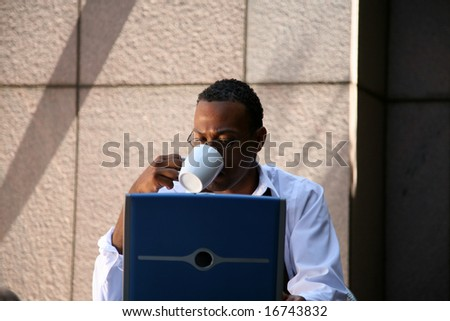 a business man works from his office at an outdoor coffee shop with his laptop and wireless internet connection - stock photo