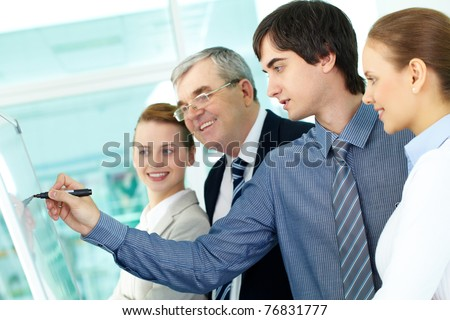 A business man writing on whiteboard with a highlighter while explaining something to colleagues - stock photo