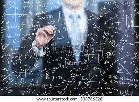A business person is writing down math formulas on the glass screen in the evening modern panoramic office. - stock photo