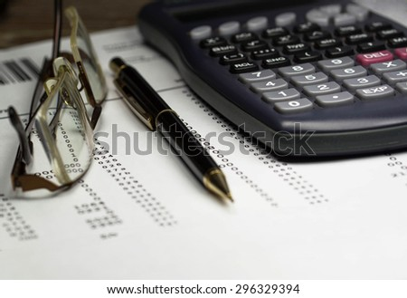 A business plan lying on a desk with a calculator, ballpoint pen and pair of reading glasses. - stock photo