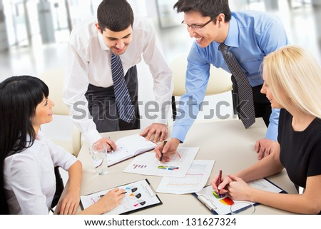 A business team of four plan work in office