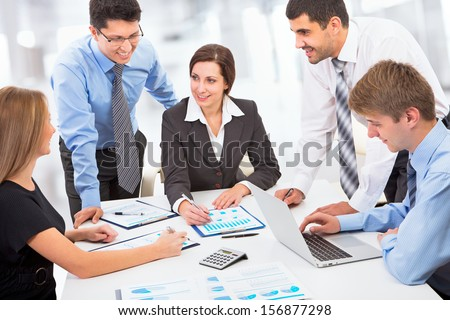 A business team of four plan work in office - stock photo