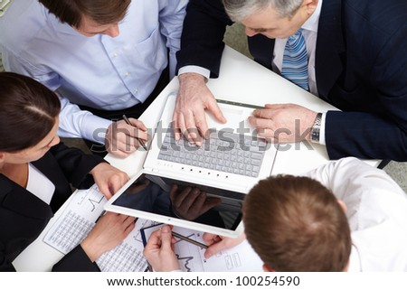 A business team of four sitting at table and planning - stock photo