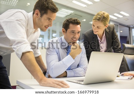 A business team of three in office working on computer - stock photo