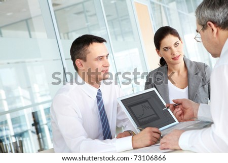 A business team of three sitting at table and planning work - stock photo