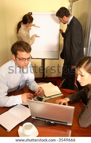 A business team of two men and two women, work on putting together a business proposal for a client. - stock photo