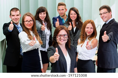 A business team standing in office after a successful business with thump up