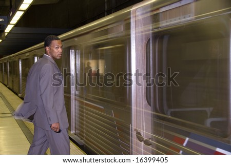 A business traveler waits for a passing subway train to stop.