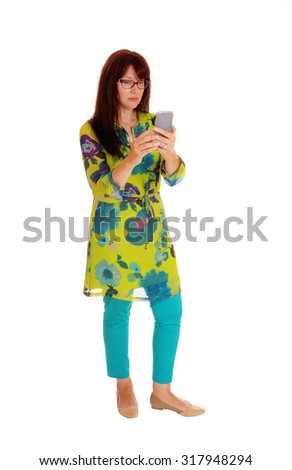 A business woman in a colorful dress dialing on her cell phone, standing isolated for white background.