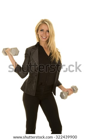 A business woman in her suit jacket working out with weights.