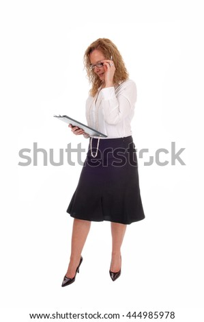 A business woman standing in a black skirt white blouse holdingher clipboard, looking at, isolated for white background. - stock photo