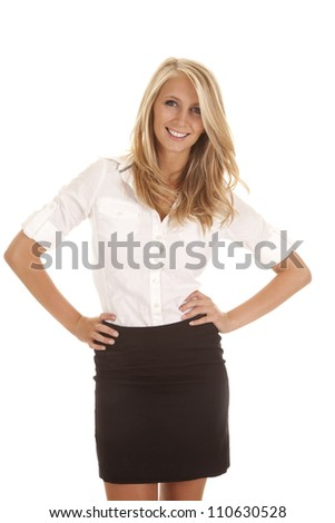 A business woman standing with a smile on her face with her hands on her hips - stock photo