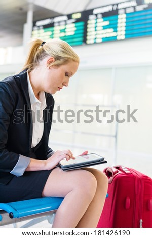a business woman using her tablet computer at an airport. mobility and communication in business. roaming charges when abroad. - stock photo