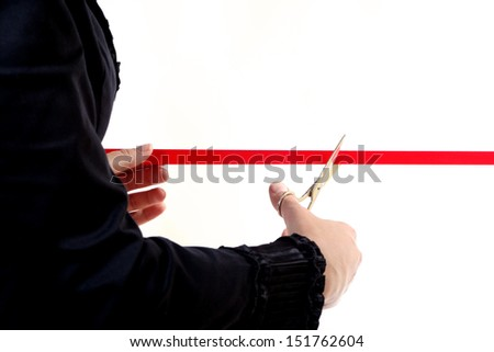 A business woman wearing a black suit cutting a red ribbon with a pair of shiny silver scissors on a white background.  - stock photo