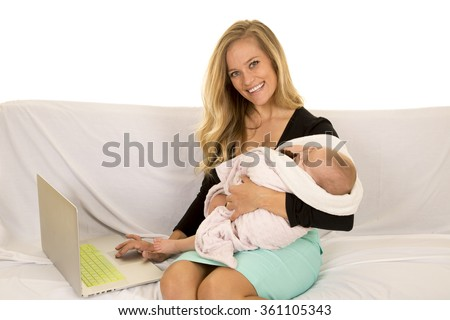 a business woman with a big smile, working, with her baby in her arms asleep.