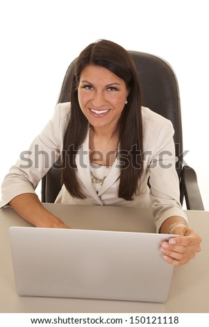 A business woman with a smile on her face working at her desk, on her laptop.