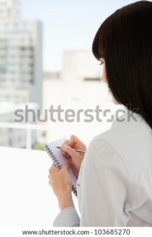 A business woman with her back to the camera begins to write down information that she has though of - stock photo