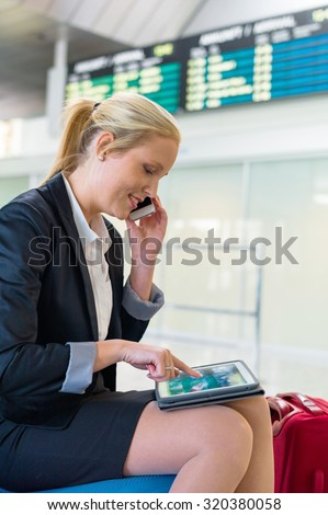 a business woman with her cell phone and a tablet computer at an airport. mobility and communication in business. roaming charges when abroad.
