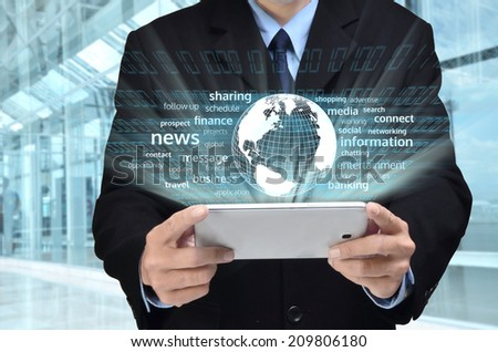 A businessman accessing internet and information technology via tablet / gadget in his hand