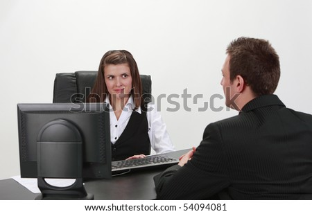 A businessman and a businesswoman at an interview in an office.
